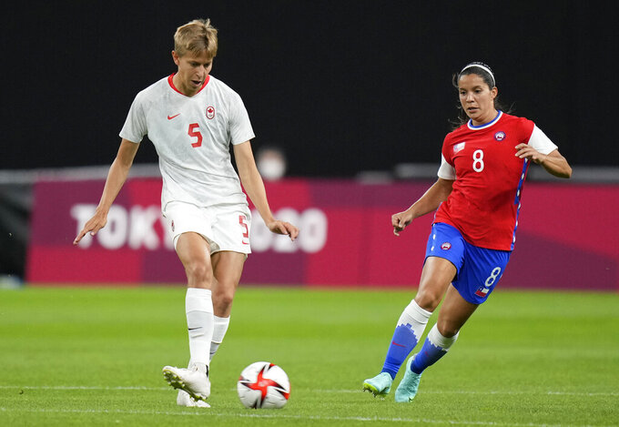 Canada's Quinn, left, and Chile's Karen Araya vie for the ball during a women's soccer match at the 2020 Summer Olympics, Saturday, July 24, 2021, in Sapporo, Japan. (AP Photo/Silvia Izquierdo)