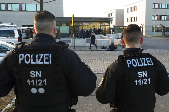 Police Officers stand in front of the court entrance prior the beginning of the trial against Alaa S. of Syria in the higher regional court in Dresden, Germany, Monday, March 18, 2019. The asylum seeker is accused together with now fugitive Iraqi asylum-seeker of having killed 35-year-old Daniel H. in Chemnitz on Aug. 26, 2019.  (AP Photo/Jens Meyer)