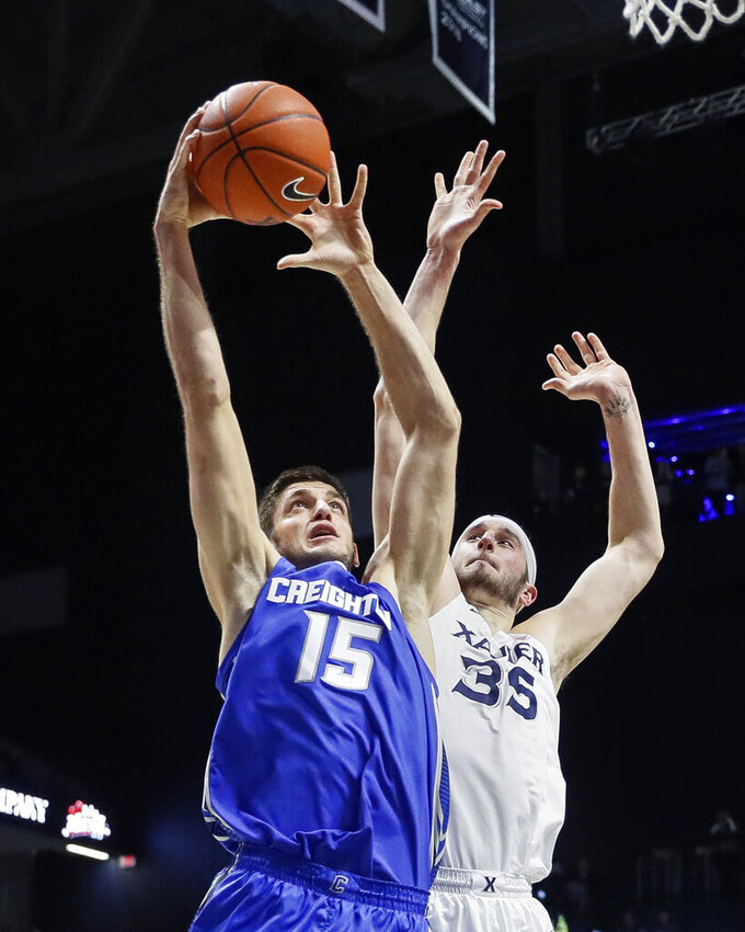 Creighton's Martin Krampelj (15) shoots against Xavier's Zach Hankins (35) during the first half of an NCAA college basketball game Wednesday, Feb. 13, 2019, in Cincinnati. (AP Photo/John Minchillo)