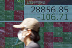 A woman wearing a protective mask rides a bicycle in front of an electronic stock board showing Japan's Nikkei 225 index at a securities firm Wednesday, June 9, 2021, in Tokyo. Asian shares were mixed on Wednesday after China reported a big jump in factory gate prices at a time when inflation is a top investor concern.(AP Photo/Eugene Hoshiko)