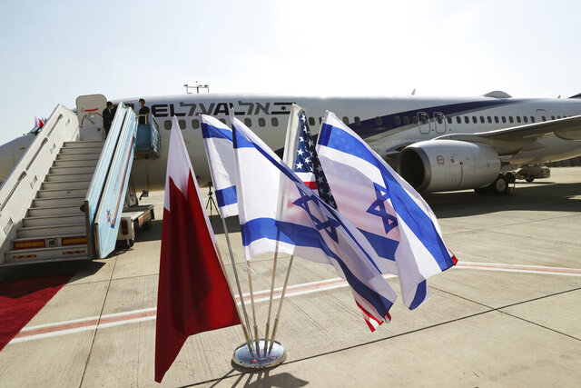 The national flags of Bahrain, Israel and America, flutter in near the Israeli flag carrier El Al plane that will fly an Israeli delegation, accompanied by U.S. aides, to Bahrain to formalise relations and broaden Gulf cooperation, at Ben Gurion airport in Lod, near Tel Aviv, Israel Sunday, Oct. 18, 2020. (Ronen Zvulun/Pool Photo via AP)