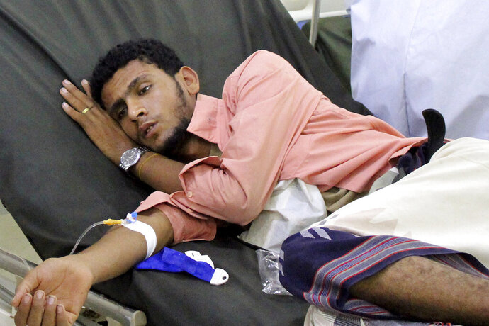 In this May 12, 2020 photo, a Yemeni man receives treatment as he lies on a bed at a hospital in Aden, Yemen. People have been dying by the dozens each day in southern Yemen's main city, Aden, many of them with breathing difficulties, say city officials. Blinded with little capacity to test, health workers fear the coronavirus is running out of control, feeding off a civil war that has completely broken down the country. (AP Photo/Wail al-Qubaty)