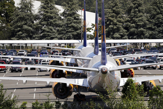 FILE - In this Thursday, Aug. 15, 2019, file photo, three grounded Boeing 737 Max airplanes, built for Icelandair, sit parked in a lot normally used for cars in an area adjacent to Boeing Field, in Seattle. Federal safety regulators say they'll keep full control over approving each new Boeing 737 Max built since the planes were grounded in March. (AP Photo/Elaine Thompson, File)