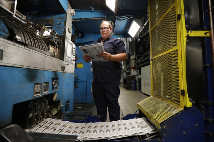In this Tuesday, Aug. 6, 2019, photo, press operator Robin Yeager looks over the registration of a newspaper in Youngstown, Ohio. The Youngstown paper announced in June it would cease publication Saturday, Aug. 31, because of financial struggles, but the paper will be printed by the Tribune Chronicle, which has bought The Vindicator name, subscriber list and website from owners of the Youngstown publication. (AP Photo/Tony Dejak)