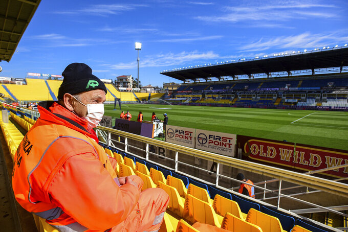 A man wears a mask as he sits in the stands ahead of a Serie A soccer match between Parma and Spal was scheduled to be played, in Parma, northern Italy, Sunday, March 8, 2020. Parma and Spal players were ready to enter the field at Ennio Tardini stadium in Parma when they received the news that Italy's sports minister Vincenzo Spadafora said that the country's football federation should consider suspending the games. (Piero Cruciatti/LaPresse via AP)