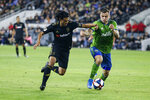 Los Angeles FC forward Carlos Vela, left, vies against Seattle Sounders forward Jordan Morris during the second half of the MLS soccer Western Conference final Tuesday, Oct. 29, 2019, in Los Angeles. The Sounders won 3-1. (AP Photo/Ringo H.W. Chiu)