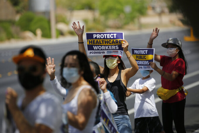 Healthcare workers protest what they say are unsafe working conditions and demand OSHA to intervene outside of MountainView hospital Thursday, April 30, 2020, in Las Vegas. (AP Photo/John Locher)