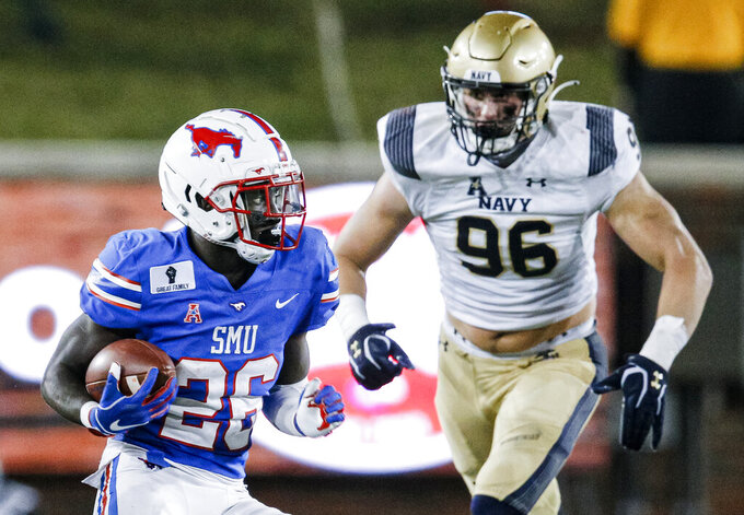SMU running back Ulysses Bentley IV (26) carries the ball as Navy defensive tackle Jackson Perkins (96) defends during the first half of an NCAA college football game, Saturday, Oct. 31, 2020, in Dallas. (AP Photo/Brandon Wade)