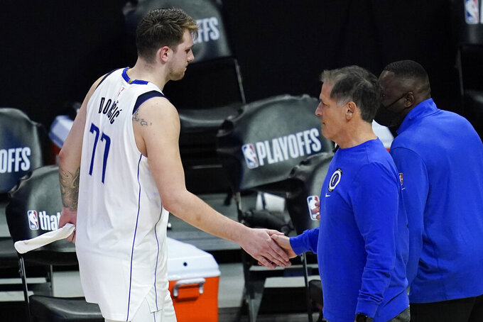 FILE- In this Sunday, June 6, 2021, file photo, Dallas Mavericks guard Luka Doncic (77) slaps hands with owner Mark Cuban after losing in Game 7 of an NBA basketball first-round playoff series against the Los Angeles Clippers in Los Angeles, Calif. Cuban is suddenly without a coach and general manager after the Mavericks were a model of stability in the NBA for more than a decade. The owner's next moves figure to be all about superstar Luka Doncic following coach Rick Carlisle's decision to quit a day after the club announced the departure of longtime GM Donnie Nelson.  (AP Photo/Ashley Landis, File)