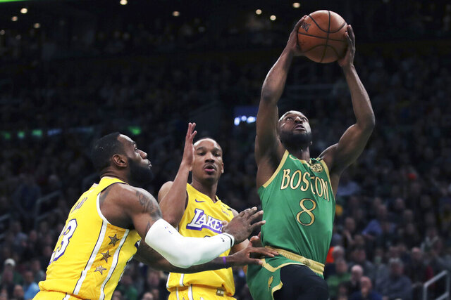 Boston Celtics guard Kemba Walker (8) drives to the basket past Los Angeles Lakers guard Avery Bradley (11) and forward LeBron James (23) during the first half of an NBA basketball game in Boston, Monday, Jan. 20, 2020. (AP Photo/Charles Krupa)