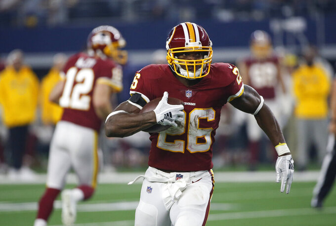 FILE - In this Nov. 22, 2018, file photo, Washington Redskins running back Adrian Peterson (26) carries against the Dallas Cowboys during the second half of an NFL football game in Arlington, Texas. A person with knowledge of the move says the Redskins agreed to re-sign Peterson to an $8 million, two-year deal. The person spoke to The Associated Press on condition of anonymity Wednesday, March 13, because the team hadn't announced the contract. (AP Photo/Ron Jenkins)