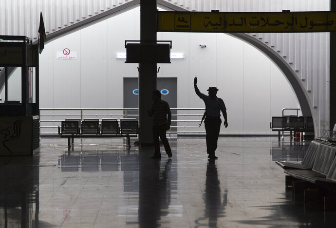 FILE - In this Aug. 20, 2011, file, photo taken on a government-organized tour, a guard waves to fellow officers in the main lobby of the international airport in Tripoli, Libya. The only functioning airport in Libya's capital suspended its operations after coming under attack Wednesday, Jan. 22, 2020, airport authorities said, despite a tenuous truce that world powers have pushed warring parties to respect. Authorities at Mitiga airport said six Grad missiles crashed into the tarmac. (AP Photo/Dario Lopez-Mills, File)