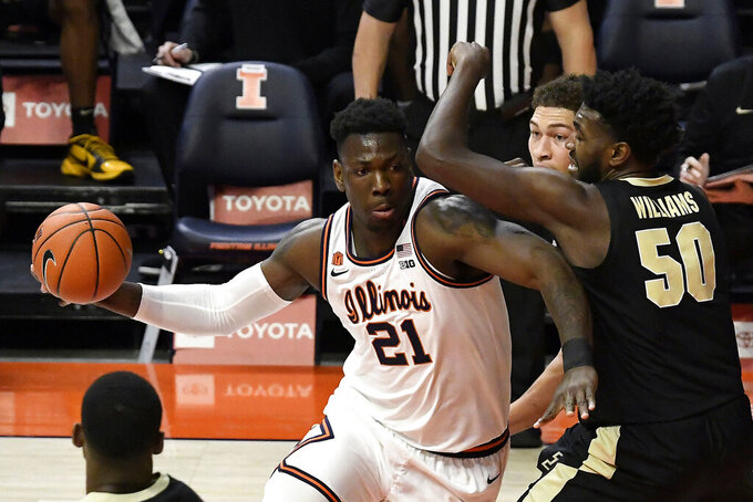 Illinois center Kofi Cockburn (21) does to the basket as he is pressured by Purdue's forward Trevion Williams (50) in the first half of an NCAA college basketball game Saturday, Jan. 2, 2021, in Champaign, Ill. (AP Photo/Holly Hart)