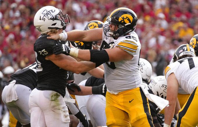 Iowa State linebacker Mike Rose (23) holds back Iowa defensive lineman Logan Lee (85) during the second half of an NCAA college football game, Saturday, Sept. 11, 2021, in Ames, Iowa. Iowa won 27-17. (AP Photo/Matthew Putney)