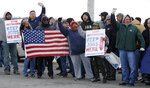 General Motors employees gather outside the plant for a protest, Wednesday, March 6, 2019, in Lordstown, Ohio. General Motors' sprawling Lordstown assembly plant near Youngstown is ending production of the Chevrolet Cruze sedan, ending for now more than 50 years of auto manufacturing at the site. (AP Photo/Tony Dejak)