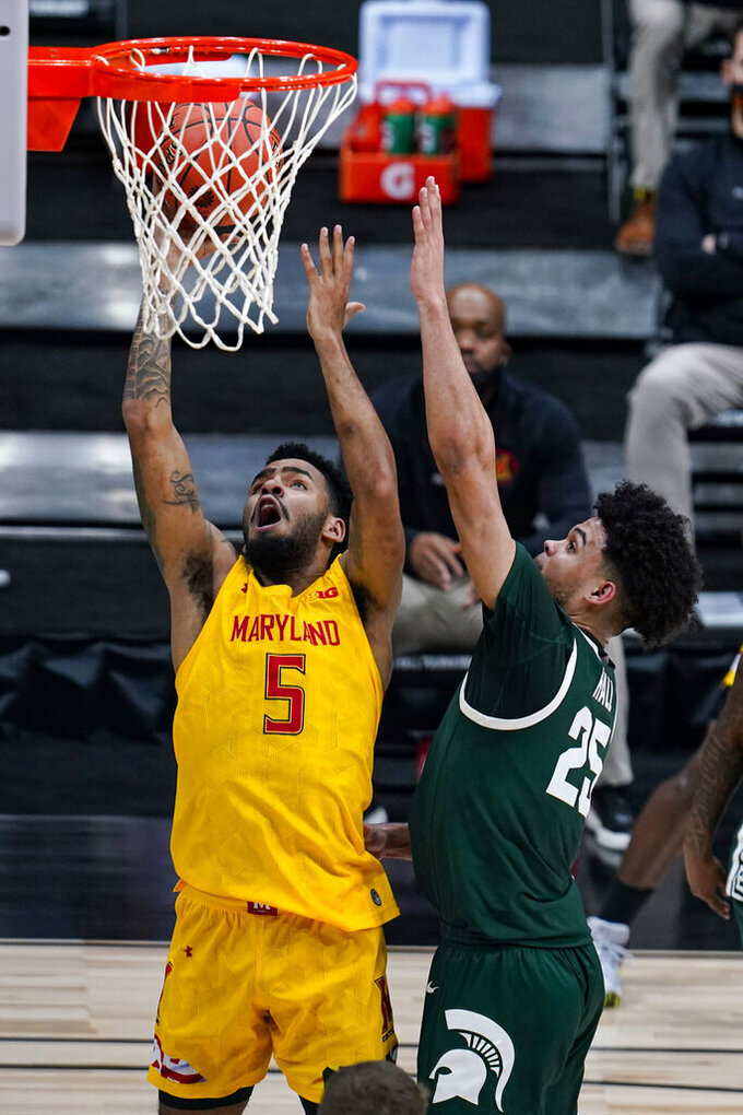 Maryland guard Eric Ayala (5) shoots over Michigan State forward Malik Hall (25) in the second half of an NCAA college basketball game at the Big Ten Conference tournament in Indianapolis, Thursday, March 11, 2021. Maryland defeated Michigan State 68-57. (AP Photo/Michael Conroy)