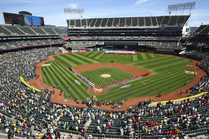 "FILE - The Los Angeles Angels and Oakland Athletics stand for the national anthem at the Oakland Coliseum prior to an opening day baseball game in Oakland, Calif., in this Thursday, March 29, 2018, file photo.Major League Baseball instructed the Athletics to explore relocation options as the team tries to secure a new ballpark it hopes will keep the club in Oakland in the long term. MLB released a statement Tuesday, May 11, 2021, expressing its longtime concern that the current Coliseum site is ""not a viable option for the future vision of baseball."" (AP Photo/Ben Margot, File)"