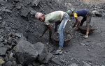 In this Oct. 23, 2019, photo, laborers fill baskets with coal before loading it into trucks for transportation in the village of Godhar in Jharia,, a remote corner of eastern Jharkhand state, India. The fires started in coal pits in eastern India in 1916. More than a century later, they are still spewing flames and clouds of poisonous fumes into the air, forcing residents to brave sizzling temperatures, deadly sinkholes and toxic gases. (AP Photo/Aijaz Rahi)