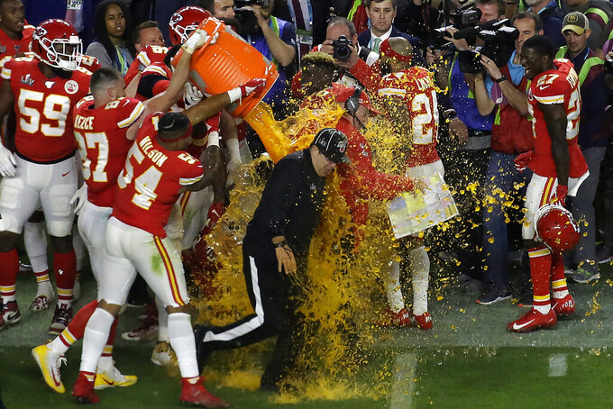 Kansan City Chiefs' players pour a cooler of Gatorade on head coach Andy Reid and members of the coaching staff, after winning the NFL Super Bowl 54 football game Sunday, Feb. 2, 2020, in Miami Gardens, Fla. The Chiefs' defeated the San Francisco 49ers 31-20. (AP Photo/Brynn Anderson)