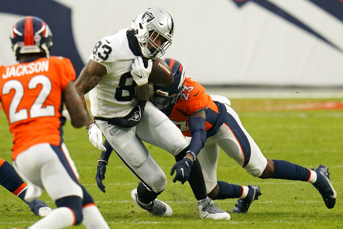 Denver Broncos cornerback Michael Ojemudia (23) forces Las Vegas Raiders tight end Darren Waller (83) to fumble during the first half of an NFL football game, Sunday, Jan. 3, 2021, in Denver. (AP Photo/Jack Dempsey)