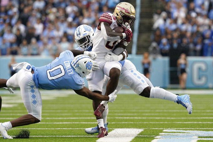 North Carolina defensive lineman Tomari Fox, rear, and defensive back Ja'Qurious Conley (0) tackle Florida State running back Jashaun Corbin (0) during the second half of an NCAA college football game in Chapel Hill, N.C., Saturday, Oct. 9, 2021. (AP Photo/Gerry Broome)