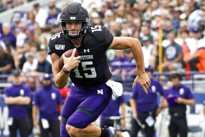 FILE - In this Sept. 21, 2019, file photo, Northwestern quarterback Hunter Johnson (15) runs the against Michigan State during the first half of an NCAA college football game in Evanston, Ill. Northwestern hopes to get some payback against Michigan State. The Wildcats will have their opportunity Friday night when they open at home against the Spartans in what they hope kicks off a run toward their third Big Ten West championship in four years. (AP Photo/David Banks, File)