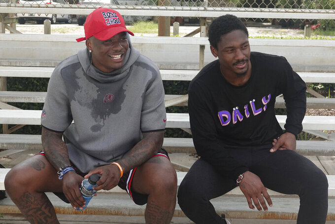 FILE - In this May 27, 2020, file photo, Washington Redskins quarterback Dwayne Haskins, left, sits with the Buffalo Bills wide receiver Stefon Diggs during a workout at Holiday Park in Fort Lauderdale, Fla. The Chicago Bears, Tennessee Titans and Los Angeles Rams all decided to end their offseason programs even with the NFL allowing two more weeks to keep working.  So did the Houston Texans, Arizona Cardinals and Washington Redskins. Turns out there's only so much that can be done virtually. Video chats don't quite replace being able to pull a coach aside for an extra 15 minutes after a meeting. To Redskins quarterback Dwayne Haskins, that's been the biggest challenge preparing for his second NFL season with a new coach. (Joe Cavaretta/South Florida Sun-Sentinel via AP, File)