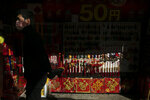 In this Feb. 13, 2020, photo, a man wearing a mask walks past a street kiosk selling souvenirs in Yokohama's Chinatown, near Tokyo. A top Olympic official made clear Friday the 2020 Games in Tokyo will not be cancelled despite the virus that has spread from China. (AP Photo/Jae C. Hong)