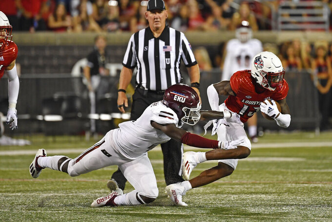 Louisville defensive back Kei'Trel Clark (13) runs from the grasp of Eastern Kentucky defensive back Davion Ross, front left, during the second half of an NCAA college football game in Louisville, Ky., Saturday, Sept. 11, 2021. (AP Photo/Timothy D. Easley)