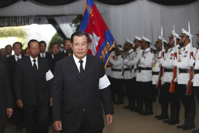 Cambodian Prime Minister Hun Sen reviews the honor guard as he arrives for a funeral ceremony of Princess Norodom Buppha Devi at a Buddhist pagoda in Phnom Penh, Cambodia, Wednesday, Nov. 20, 2019. Buppha Devi, eldest daughter of Cambodia's late King Norodom Sihanouk and a famed dancer, died Monday, Nov. 18, 2019, at age 76. (AP Photo/Heng Sinith)
