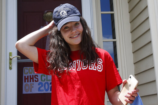 In this June 1, 2020 photo, high school graduate Lizzie Quinlivan wears a Georgetown University cap at her home in Hingham, Mass. Quinlivan has opted to attend closer-to-home Georgetown instead of colleges on the west coast which were on her original wish-list. As students make college plans for this fall, some U.S. universities are seeing surging interest from in-state students looking to stay closer to home amid the coronavirus pandemic. (AP Photo/Elise Amendola)