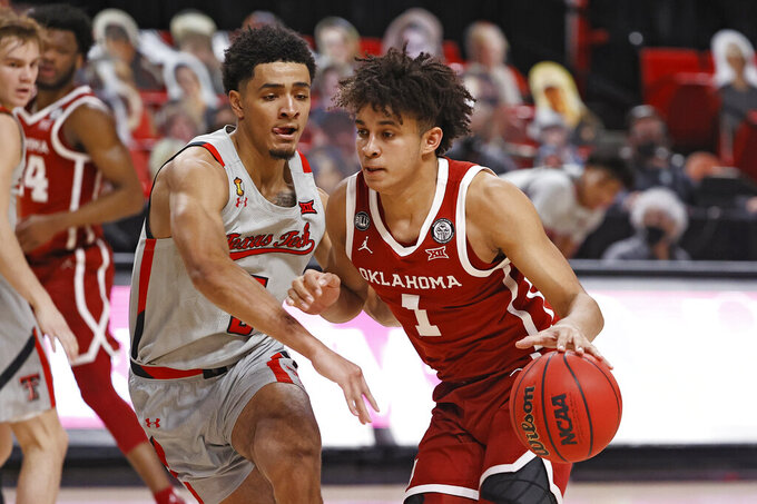 Oklahoma's Jalen Hill (1) dribbles around Texas Tech's Micah Peavy (5) during the first half of an NCAA college basketball game Monday, Feb. 1, 2021, in Lubbock, Texas. (AP Photo/Brad Tollefson)