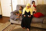 CORRECTS THE GIRLS' AGES TO 13 AND 10, RESPECTIVELY - Amina Olow, a refugee from Somalia, looks at photos of two of her eldest daughters while siting with two of her other children in her Columbus, Ohio, home on Friday, Feb. 23, 2018. The girls, Neemotallah, now 13, and Nastexo, now 10, live in Kenya with other family members. It has been 10 years since their mother has seen them.
