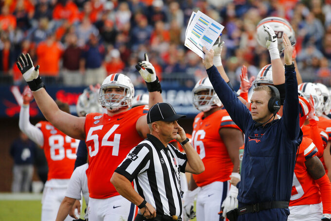 Virginia head coach Bronco Mendenhall, right, signals for a touchdown along with offensive tackle Ryan Nelson (54) as they wait on a ruling during the first half of an NCAA college football game against Duke in Charlottesville, Va., Saturday, Oct. 19, 2019. (AP Photo/Steve Helber)