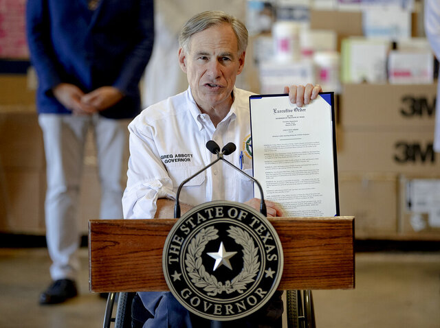 Texas Gov. Greg Abbott shows a new executive order regarding reporting data about the coronavirus during a news conference on Tuesday, March 24, 2020, in Austin, Texas. (Nick Wagner/Austin American-Statesman via AP)