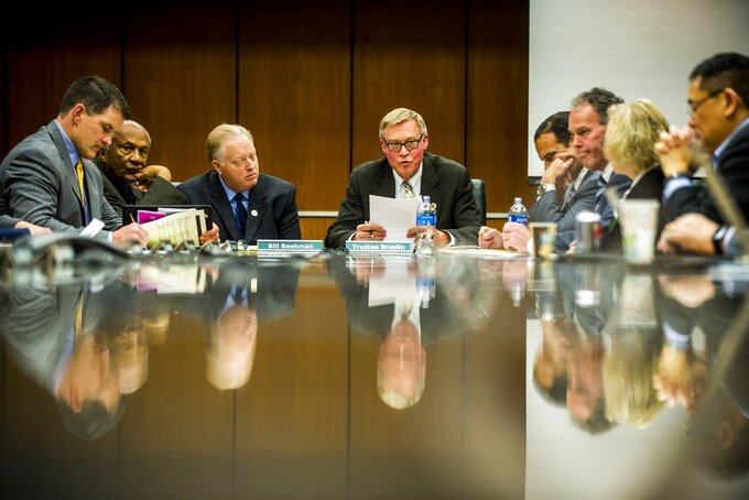 Brian Breslin, center, chairman of the Michigan State board of trustees, makes official the resignation of former President Lou Anna Simon during a special Michigan State University board of trustees meeting Friday, Jan. 26, 2018, on campus in East Lansing, Mich., where Bill Beekman was announced the acting president. Simon resigned over the school's handling of sexual abuse allegations against its disgraced former sports doctor, Larry Nassar. (Jake May/The Flint Journal-MLive.com via AP)