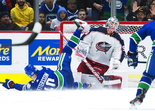 Vancouver Canucks center Elias Pettersson (40) sends a shot past Columbus Blue Jackets goaltender Elvis Merzlikins (90) during the third period of an NHL hockey game in Vancouver, British Columbia, Sunday, March 8, 2020. (Jonathan Hayward/The Canadian Press via AP)