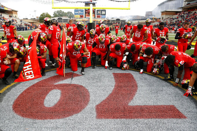 FILE - In this Oct. 27, 2018, file photo, Maryland players gather at a No. 79 painted on the field in remembrance of offensive lineman Jordan McNair, who died after collapsing on a practice field during a spring practice, before an NCAA college football game against Illinois,  in College Park, Md. Of all the things on the checklist of Maryland football coach Michael Locksley, none are more pressing than forming a bond with players who in 2018 dealt with the death of a teammate and the subsequent whirlwind of activity that transpired on and off the field. (AP Photo/Patrick Semansky, File)