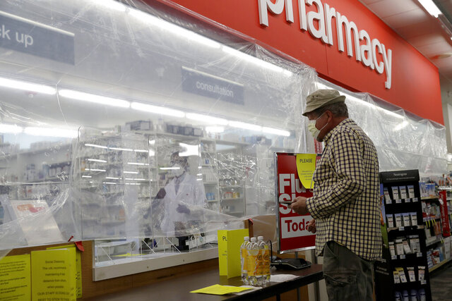 A customer waits for his medication behind a sheet of plastic installed to help curb the spread of the coronavirus at a CVS pharmacy store in Morton Grove, Ill., Tuesday, April 7, 2020. Customers and pharmacists are being separated by crates and plastic sheets during the Covid-19 pandemic. (AP Photo/Nam Y. Huh)