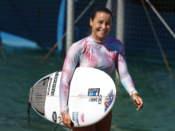 Surfer Johanne Defay, of France, leaves the water after a workout at Surf Ranch during practice rounds for the upcoming Olympics Tuesday, June 15, 2021, in Lemoore, Calif. Defay is headed to the Olympics for surfing's debut at the Games, buoyed by an upset win against reigning world champion Carissa Moore, 28, at the high-intensity Surf Ranch competition last month. Though there's much excitement and renewed enthusiasm for the women's game, the objectification, pay disparities and opportunity gap have taken its toll. Industry leaders say they're committed to righting the wrongs that have long held female surfers back in the male-dominated sport. The mental, financial and logistical roadblocks for women in surfing date back centuries. (AP Photo/Gary Kazanjian)