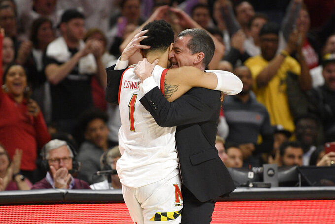 Maryland head coach Mark Turgeon, right, hugs guard Anthony Cowan Jr. (1) after Cowan came out of an NCAA college basketball game against Michigan during the second half Sunday, March 8, 2020, in College Park, Md. (AP Photo/Nick Wass)