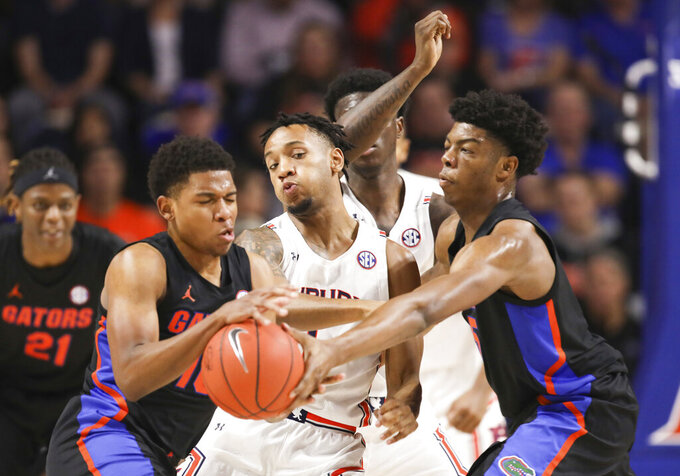 Auburn guard Jamal Johnson (1) tries to break up a pass between Florida guard Noah Locke (10) and Omar Payne (5) during the first half of an NCAA college basketball game Saturday, Jan. 18, 2020, in Gainesville, Fla. (AP Photo/Matt Stamey)