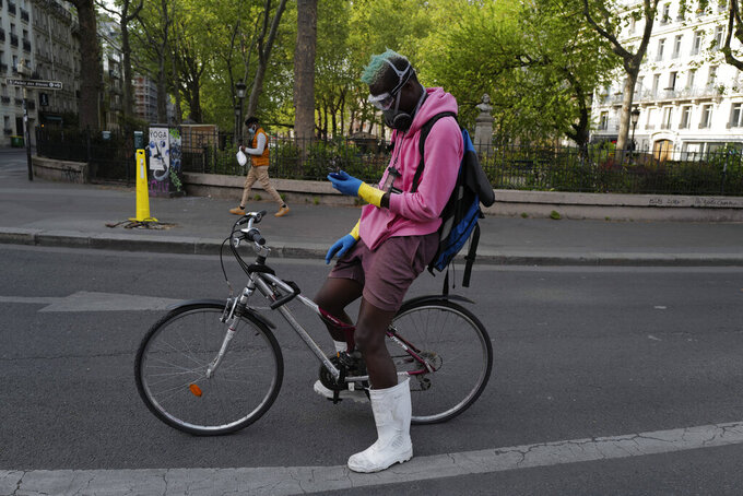 FILE - In this April 20, 2020 file photo, a delivery man, who want to name Moise, wearing protective gear checks his phones during a nationwide confinement in Paris. France is rolling out its contact-tracing app aimed to help containing the spread of the virus as life slowly returns to normal while most of its neighbors, including the UK, Germany, Italy are also about to launch their own technology. (AP Photo/Francois Mori, File)