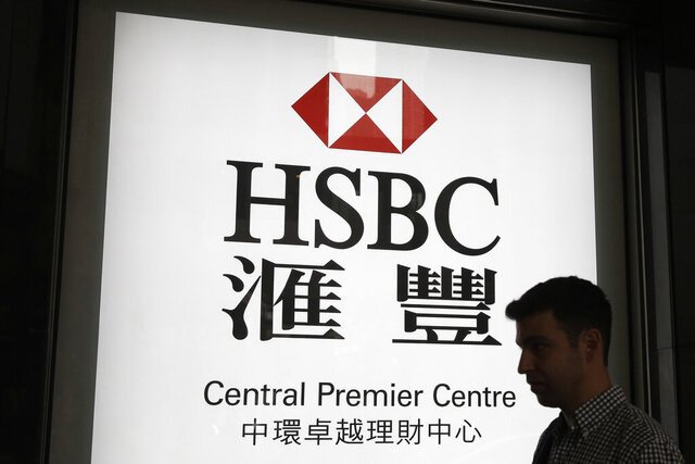 FILE - In this May 4, 2018, file photo, a man walks past a branch of HSBC bank in Hong Kong. Europe's biggest bank has reported that its net profit fell 53% in 2019 to $6 billion. London-based HSBC, whose profit is mainly from Asia, said it plans to revamp its U.S. and European business and shed $100 billion in assets to improve its profitability.  (AP Photo/Kin Cheung, File)