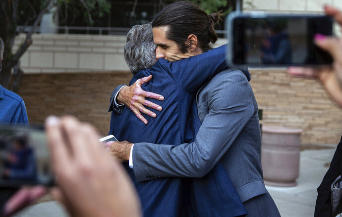Attorney Greg Kuykendall and border aid volunteer Scott Warren embrace outside the Federal Courthouse, Wednesday, Nov. 20, 2019 in Tucson, Ariz. Warren was acquitted Wednesday on charges he illegally harbored two Central American immigrants at a camp in southern Arizona operated by a humanitarian group. (Josh Galemore/Arizona Daily Star via AP)