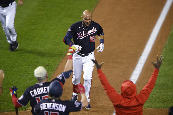 Washington Nationals' Yadiel Hernandez, top, is welcomed after his game-ending, two-run home run during the eighth inning of the second baseball game of the team's doubleheader against the Philadelphia Phillies, Tuesday, Sept. 22, 2020, in Washington. The Nationals won 8-7. (AP Photo/Nick Wass)