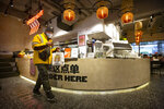A delivery driver carries a takeaway order at a Moka Bros cafe in Beijing, Friday, Feb. 14, 2020. For Valentine's Day Moka Bros, a health food eatery in Beijing, offered a special that included both a rose and a note logging the temperature of the chef that made the meal. Like many businesses in China, the restaurant has struggled to cope with the impact of a virus that has infected tens of thousands of people worldwide and sent several cities into lockdown. (AP Photo/Mark Schiefelbein)