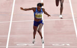 Gold medalist Dalilah Muhammad, of the United States, finishes in a new world record time in the the women's 400 meter hurdles final at the World Athletics Championships in Doha, Qatar, Friday, Oct. 4, 2019. (AP Photo/Martin Meissner)