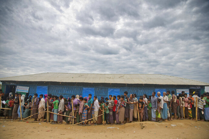 FILE - In this Nov. 15, 2017, file photo, Rohingya Muslims, who crossed over from Myanmar into Bangladesh, wait in queues to receive aid at Kutupalong refugee camp in Ukhiya, Bangladesh. Malaysia's foreign ministry says Myanmar's government must be accountable for alleged human rights abuse against the Muslim Rohingya minority so that the hundreds of thousands who fled a brutal military crackdown can return safely to the country. The call comes ahead of a meeting of Southeast Asian foreign ministers in Bangkok this week. (AP Photo/A.M. Ahad, File)