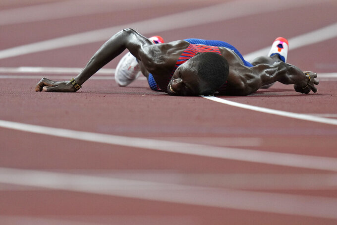 FILE - In this Aug. 6, 2021, file photo, Paul Chelimo, of United States, lies on the track after the final of the men's 5,000-meters at the 2020 Summer Olympics in Tokyo. (AP Photo/Petr David Josek, File)